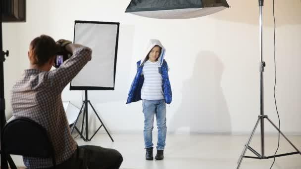 Fotograf fotografiert das Kind im Atelier.