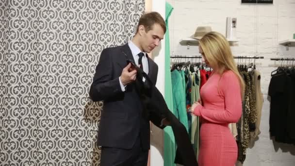 3c6bf81929f8 Αρσενικό πωλητή προσφορές γυναίκες φόρεμα. ξανθιά επιλέγει ρούχα– πλάνα  αρχείου