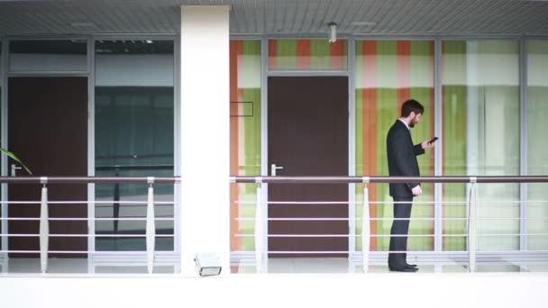 úspěšný obchodník bavit buňka telefon stoje uvnitř úřadu,