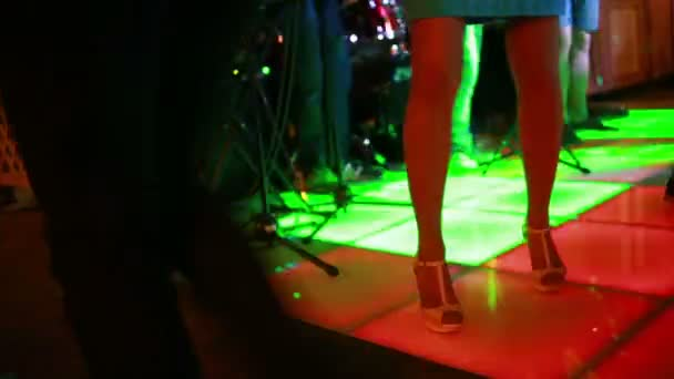 Colorful led dance floor with people dancing.