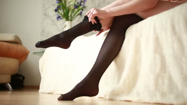 woman puts on her black nylon stockings