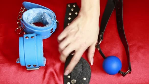 Leather accessories BDSM for sex. female hand takes sex toy. mask, handcuffs and a gag