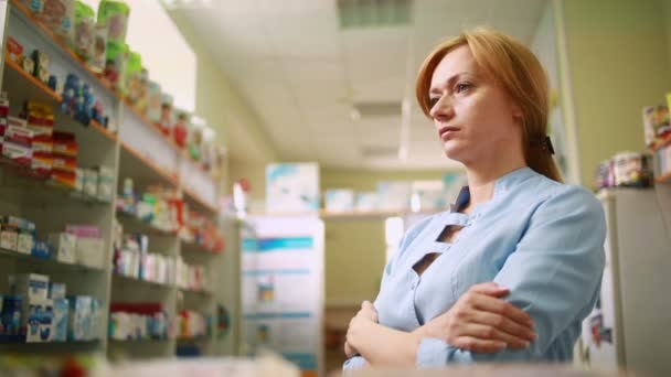 female pharmacist standing at counter in pharmacy
