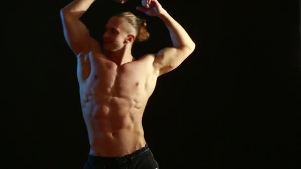 Muskelprotz Bodybuilder. Mann posiert auf schwarzem Hintergrund, zeigt seine Muskeln.