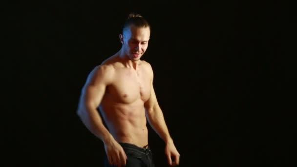 Culturista muscolare delluomo. Uomo in posa su uno sfondo nero, Mostra i suoi muscoli.