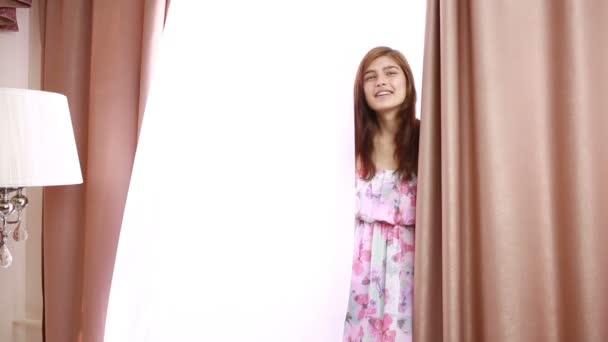 mladá radostné ženy držící závěsy otevřít podívat se oknem velké světlo doma, soustružení a úsměv na kameru, interiér. Záměr životní styl interiéru. negližé