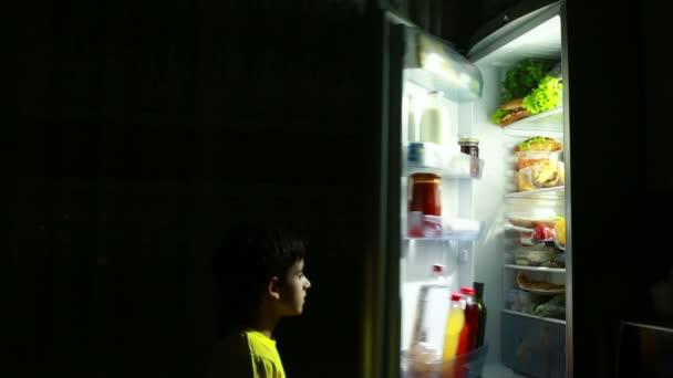 Dítě jíst svačinu před lednicí v noci. hladový boy. dort