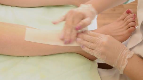 Closeup of female therapist waxing customers leg at beauty spa. depilation legs