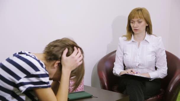 Weibliche Psychologe Notizen während psychologische Therapiesitzung. trauriges Mädchen