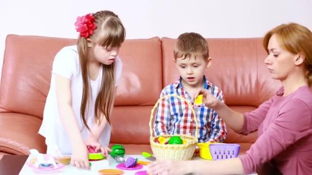 děti si hrají na gauči. dívka s Downovým syndromem. rehabilitace zdravotně postižených. matka s dětmi