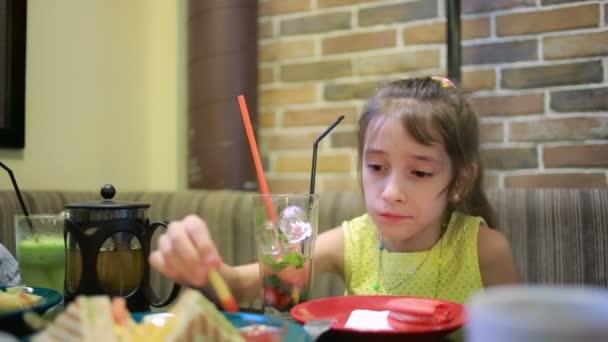 děti, dívku jíst sendviče v kavárně. hranolky