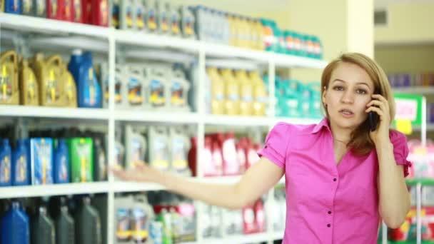 férfi eladó a boltban segít a lány, hogy megválasszák a motorolaj. Felszólítva a telefon