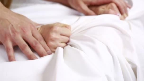 Hände eines Paares im Bett.
