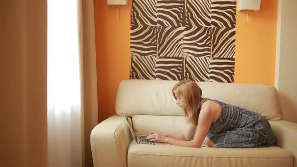 žena přes notebook v obývacím pokoji na pohovce