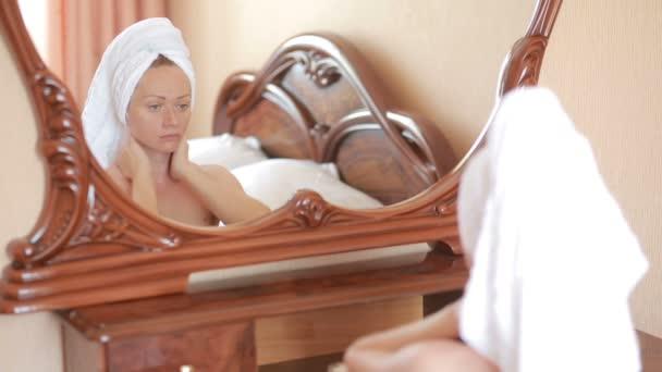 Woman applying mask moisturizing skin cream on face looking in mirror.