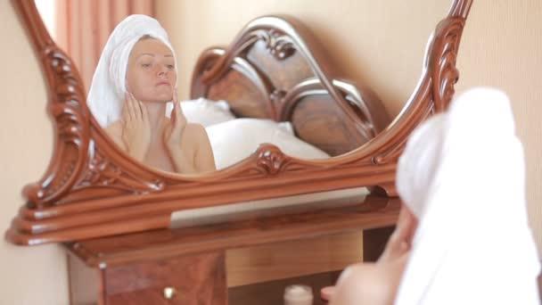 Nő alkalmazása maszk a tükörben látszó arc hidratáló arckrém.
