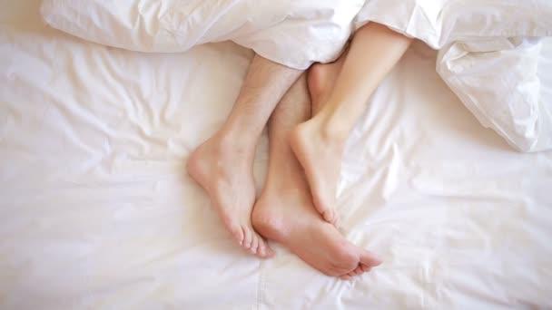 muž a žena v posteli. mužské a ženské nohy shora, bílé prádlo