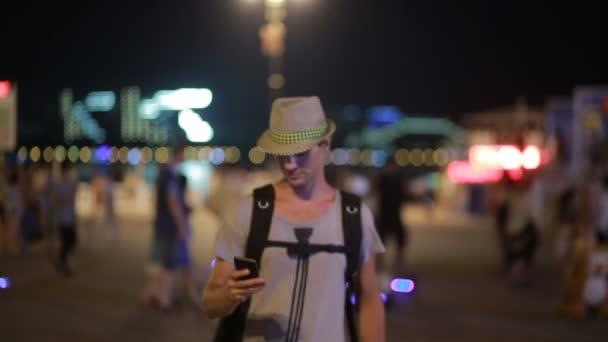 Mann mit Handy auf der Straße. ein gutaussehender Mann mit Hut und smatrtfonom