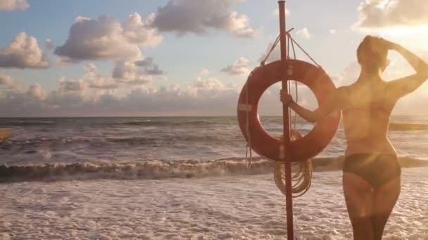 Rücken eines schönen Mädchens. Mädchen steht im Meer in der Nähe der Rettungsleine.