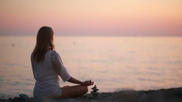 mladá žena cvičí jógu na pláži při západu slunce. klidné moře