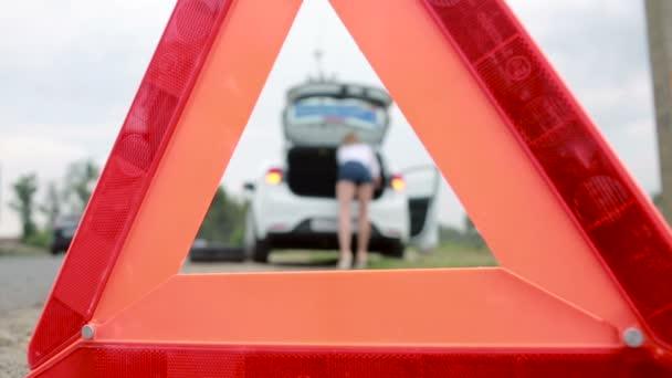 Lány változó egy kilyukadt gumiabroncs, az autó. gépkocsik javítása. baleset