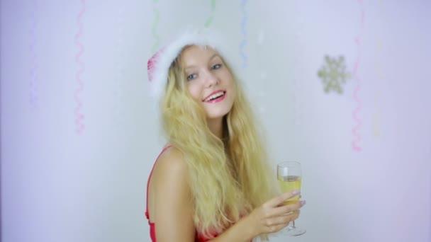 lächelnde schöne Frau mit Weihnachtsmütze schenkt Ihnen ein Glas Champagner