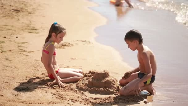 young Caucasian family is built on the beach sand castle