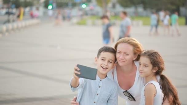 Maminka se synem a dcerou dělají selfie. rodinná fotografie na telefonu