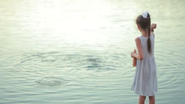 malá holčička v růžovém oblečení krmení ryb v zahradním jezírku. dítě u jezera