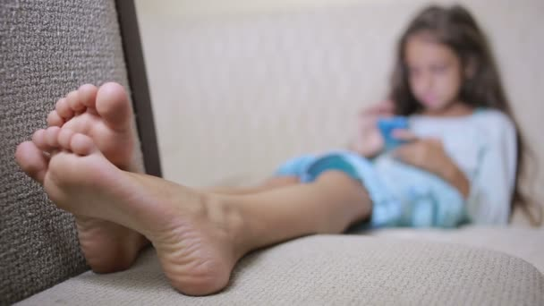 Girl child with a cell phone browses the Internet