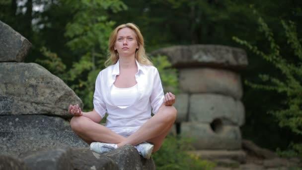 Frau sitzt und meditiert auf steinernen Dolmen