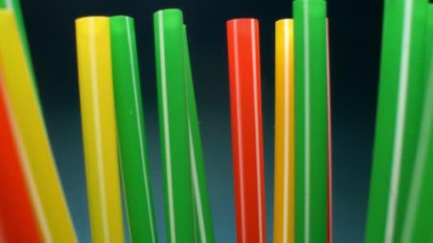Extrémní detailní záběr. mnoho pestrobarevných koktejlových brčků. modré pozadí.
