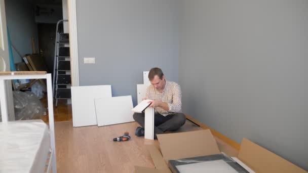 stattliche Mann sammelt Möbel zu Hause im Zimmer. Kopierraum