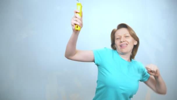 Eine fröhliche Frau mit einer Wandfarbrolle tanzt und blickt in die Kamera. Kopierraum