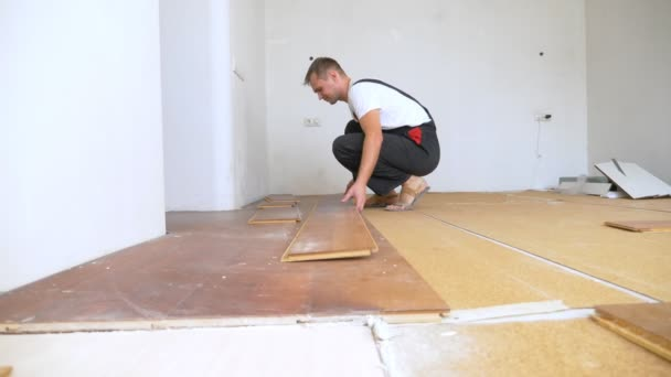 muž stavitel v montérkách bude demontovat starou laminátovou podlahu v bytě