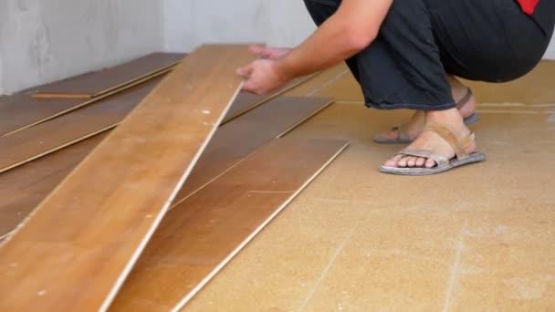 detailní záběr. samec stavitel rozbije staré laminátové podlahy v bytě