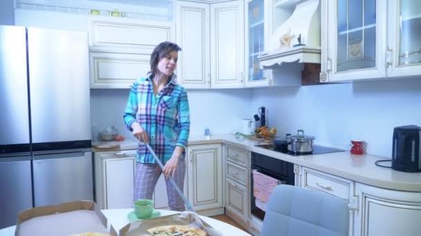 veselá žena utírá podlahu ve své kuchyni doma a tance