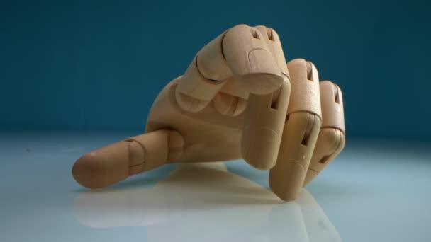 Detailní záběr. dřevěná ruka se vysmívat na modrém pozadí
