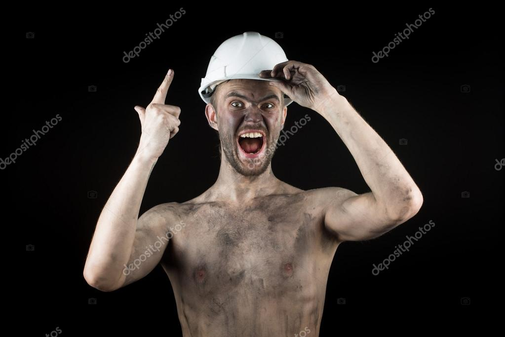 Happy dirty worker in helmet.