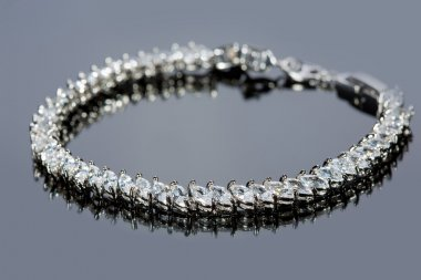 silver bracelet with diamonds on gray background.