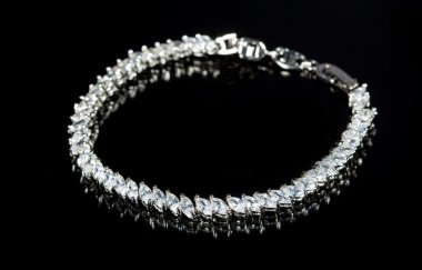 silver bracelet with diamonds on black background.