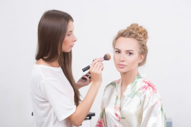 Makeup artist on applying blush on cheeks with blush brush