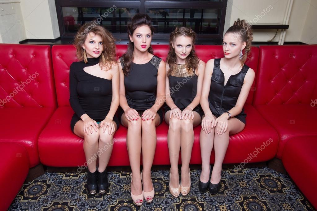 609586244 Quatro mulheres bonitas em um sofá vermelho. no interior — Fotografia de  Stock
