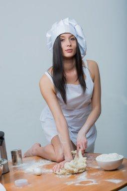 sexy woman in chef uniform knead the dough