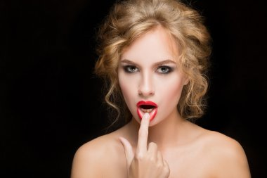 Portrait of beautiful girl with red lips. Red nails manicure. Studio shots. Black background. Beauty.
