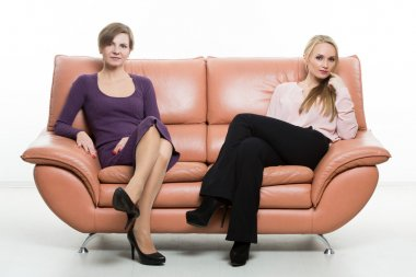 beautiful female friends on the sofa. two businesswomen. body language, gestures psychology. paired gestures. female gestures to attract men