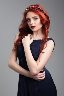 Beautiful red-haired fashion model posing in evening dress and in the diadem over dark background. female gestures of seduction. body language. touching breasts