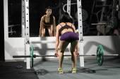 Bruneta silnému fitness sexy žena dělá činka dřepy v tělocvičně