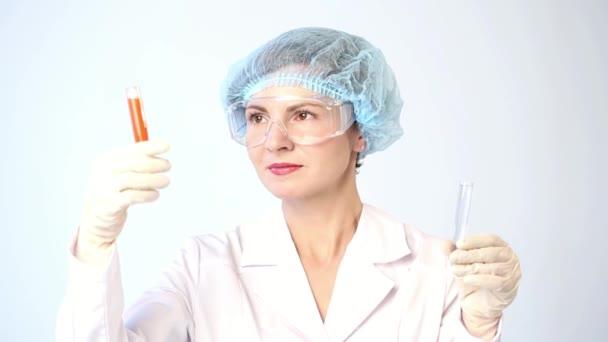 Ženské chemik porovnávání zkumavek s chemikáliemi. ochranné brýle