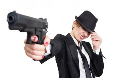 beautiful girl gangster holding a gun. Classic suit and hat. isolated on white